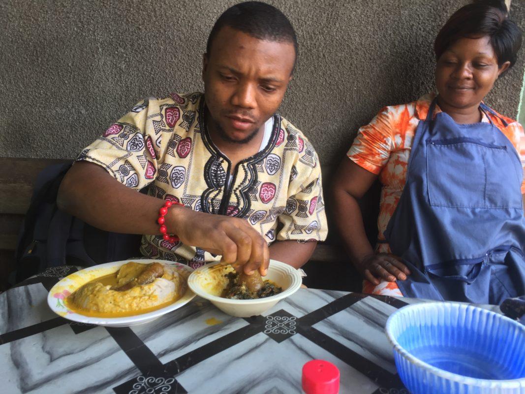 Christian Elongué entrain de manger du taro avec la sauce jaune